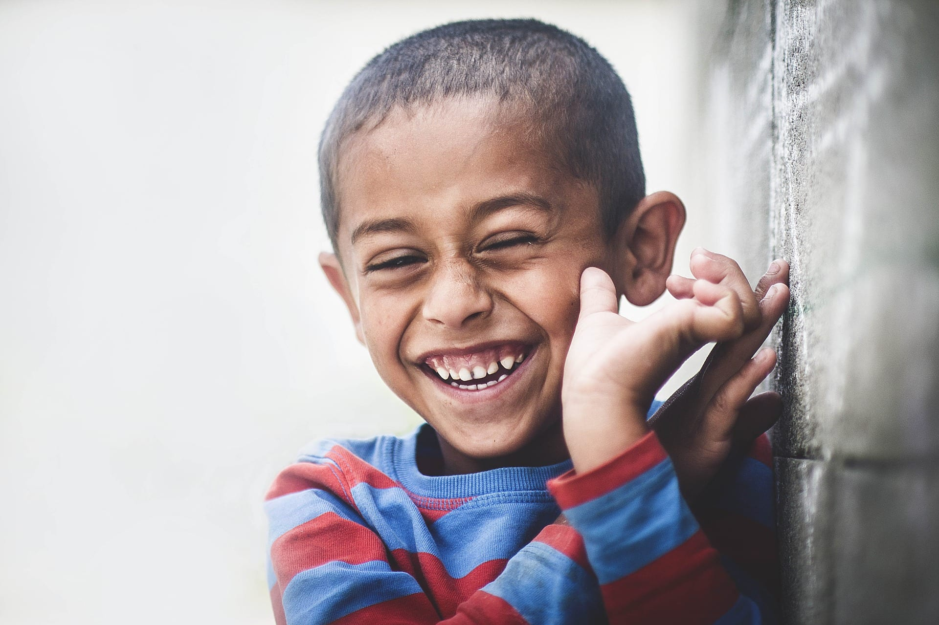 A young boy grinning widely.