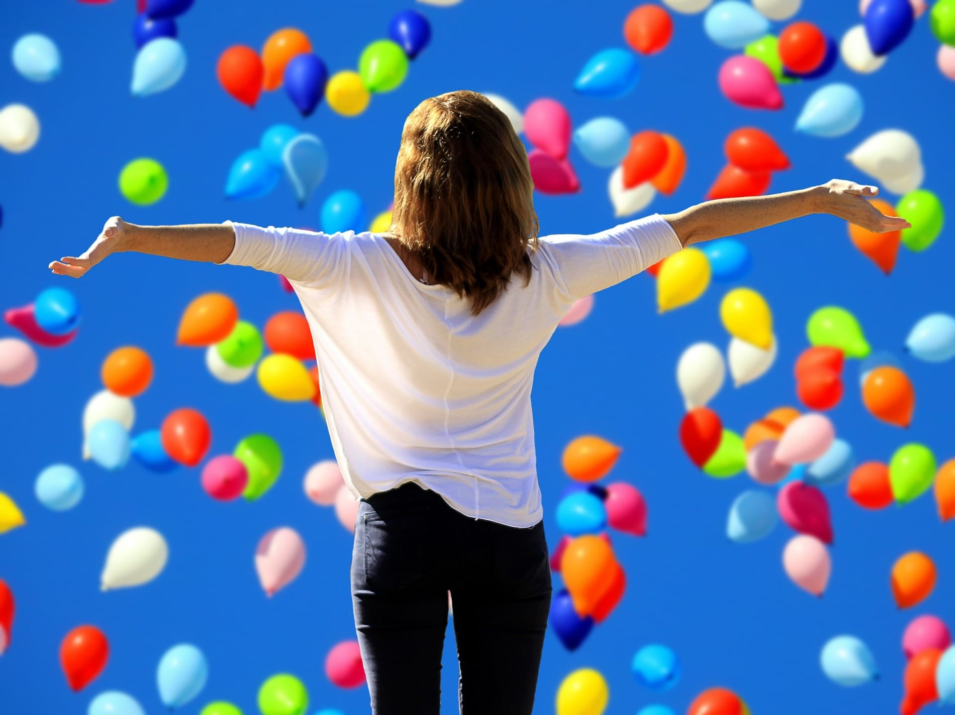 A woman triumphantly facing balloons as they fly through the sky.