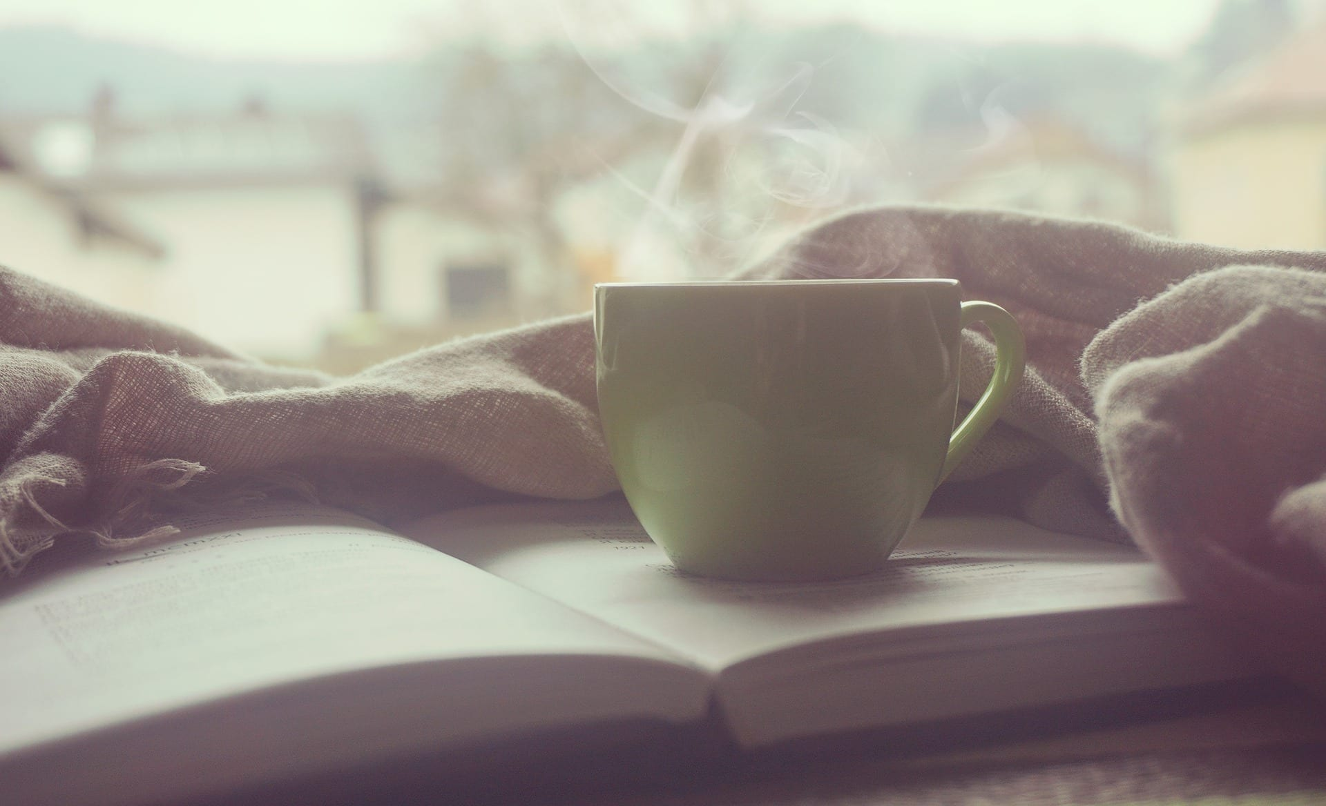 A steaming cup of coffee or tea placed directly on top of an open book. Really.