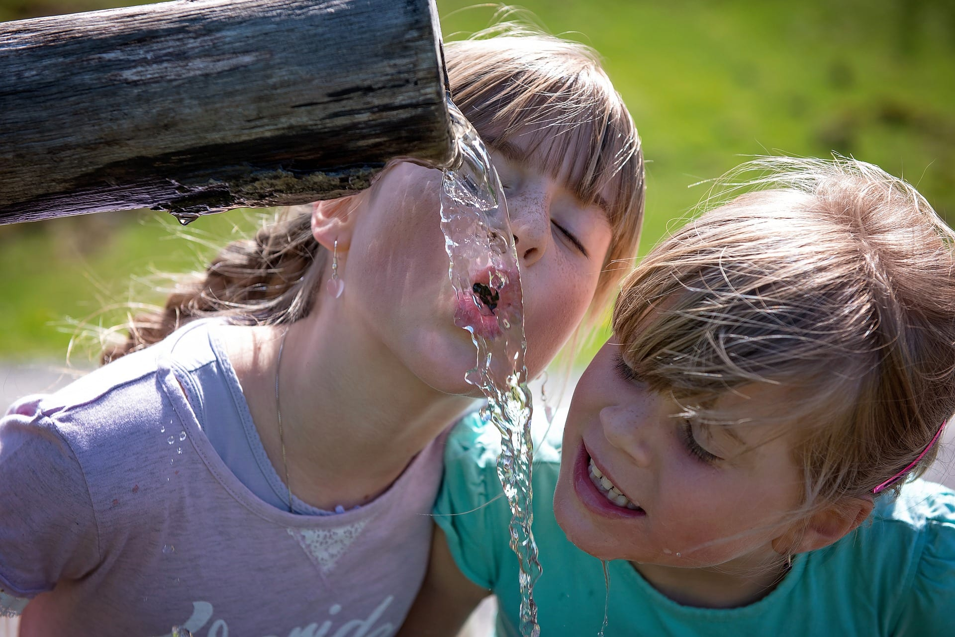 Two white children drinking from a fountain.