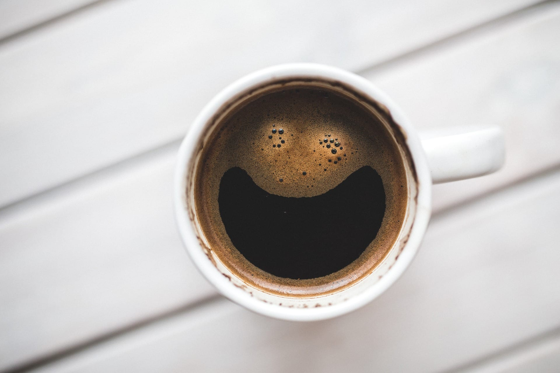 A cup of coffee that's very happy to see you!