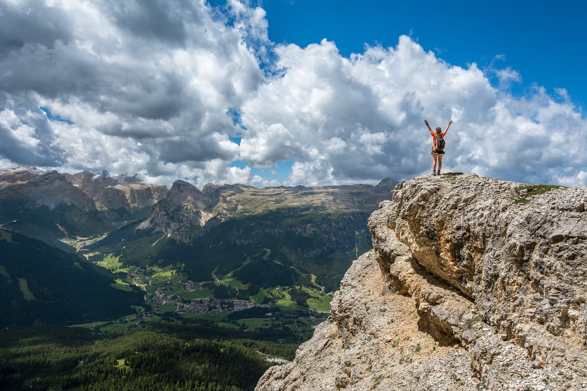 Someone standing at the top of a mountain, arms raised in triumph.