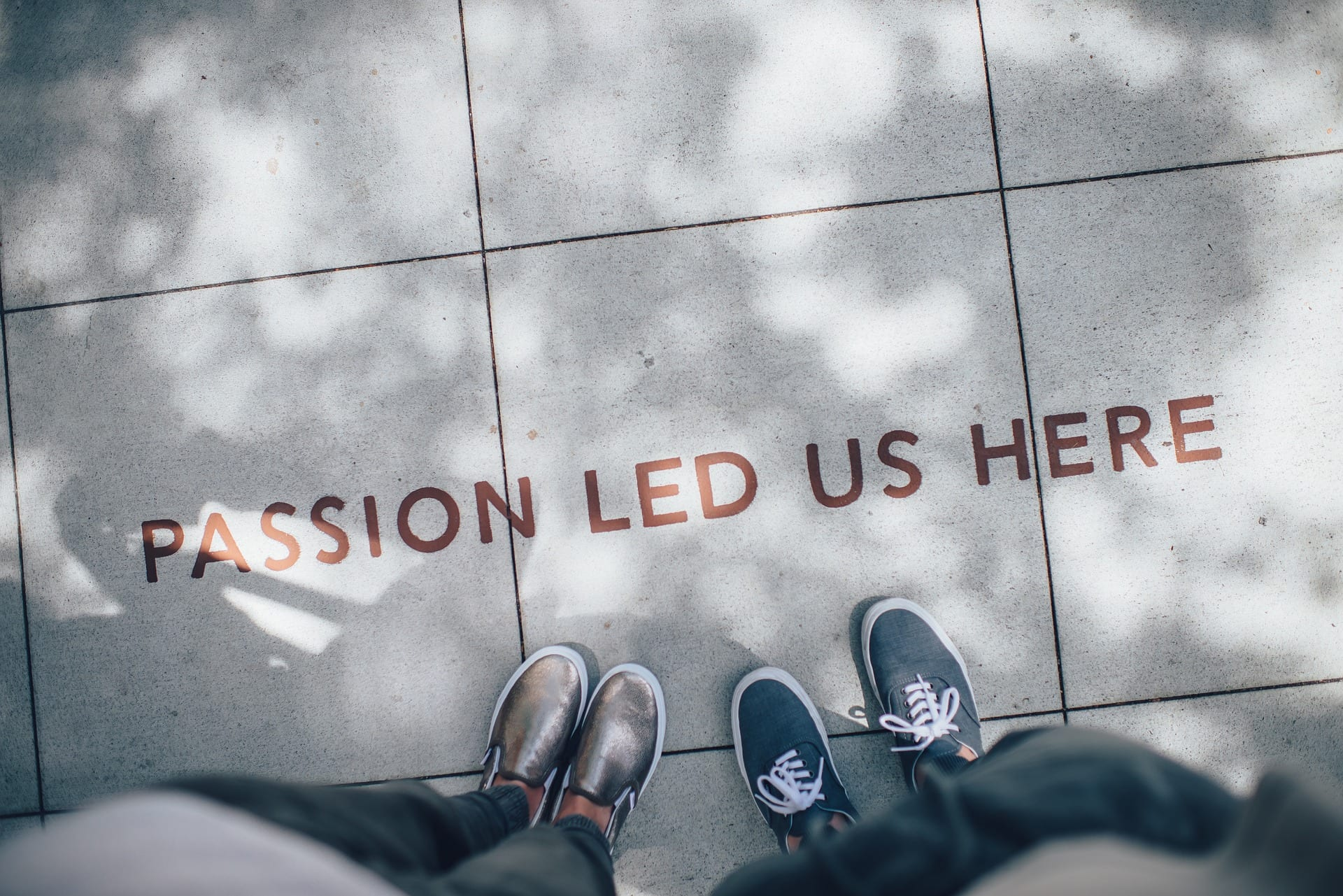 """Some feet pointing to the words """"PASSION LED US HERE"""" written on the ground."""