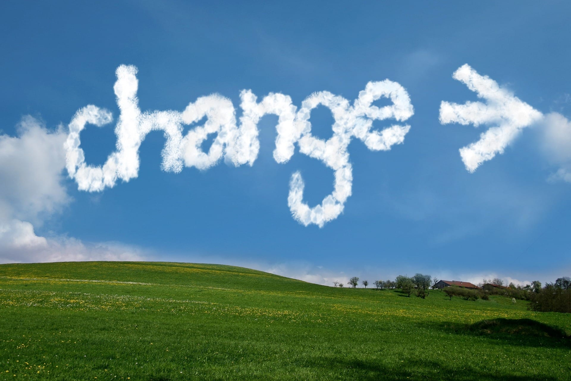"""A landscape with the word """"CHANGE,"""" along with an arrow pointing to the right, written in the clouds."""