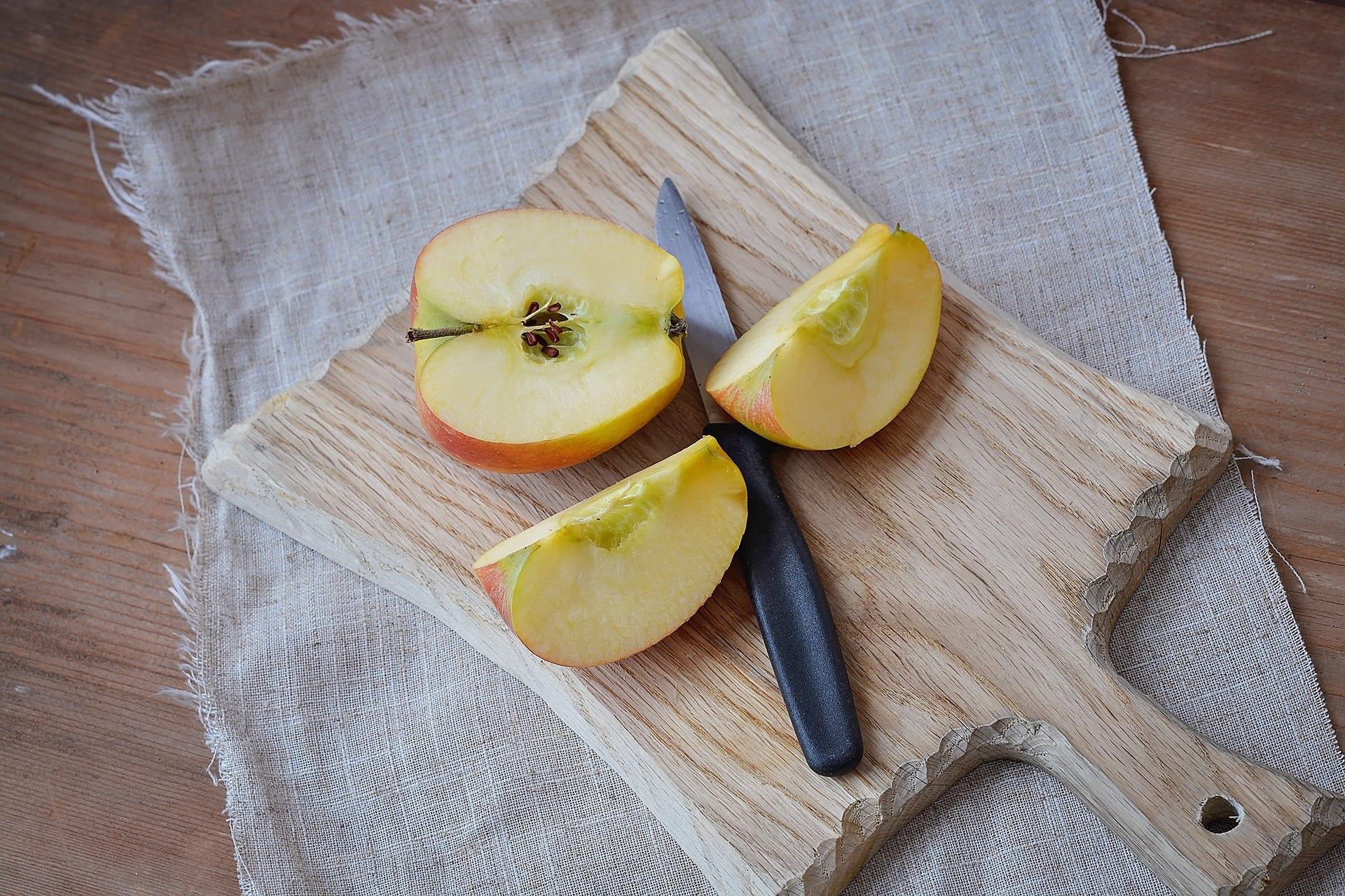 Sliced apple on a wooden cutting board.