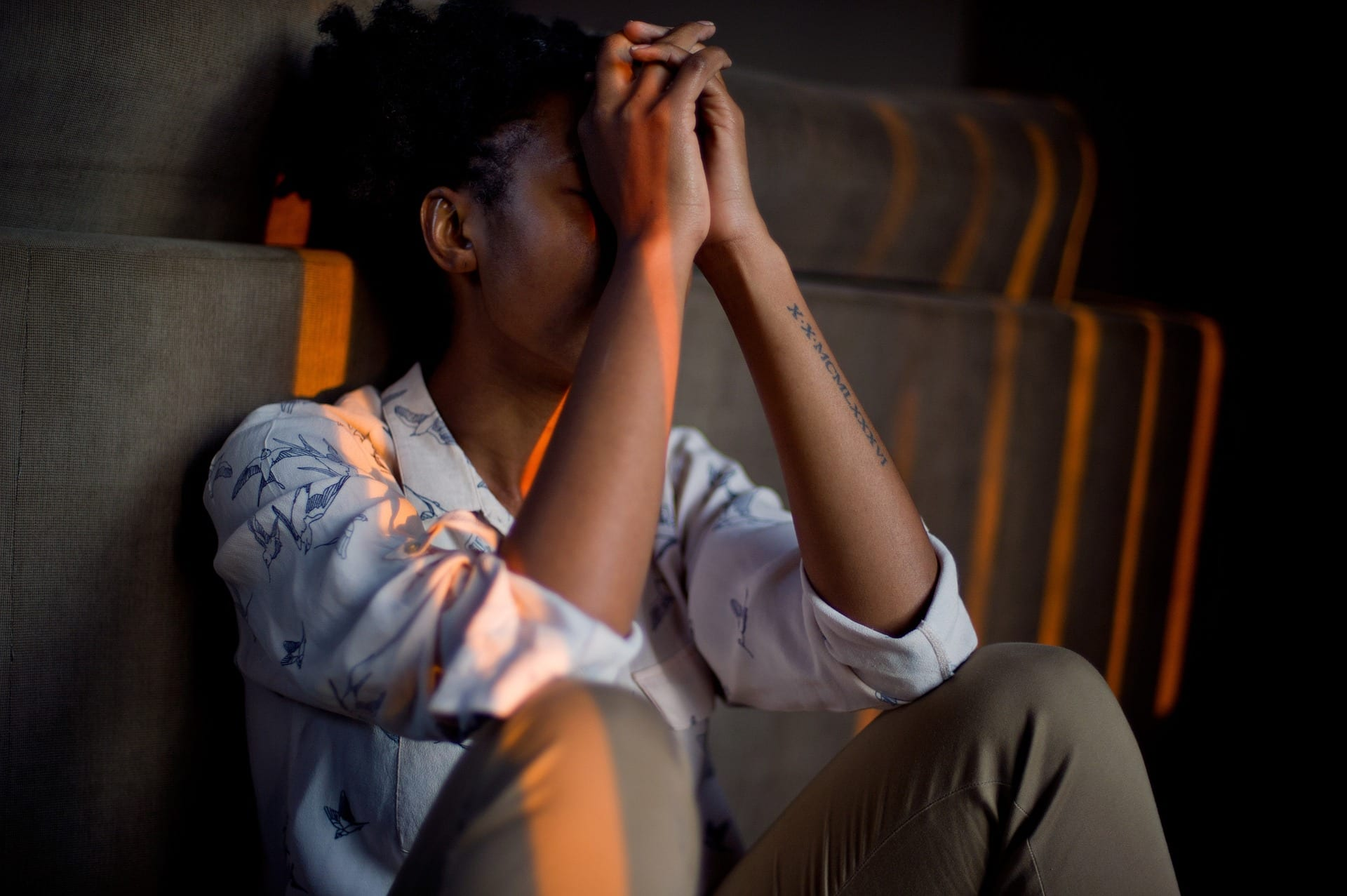 A young, dark-skinned person sitting and hiding their face, stressed.