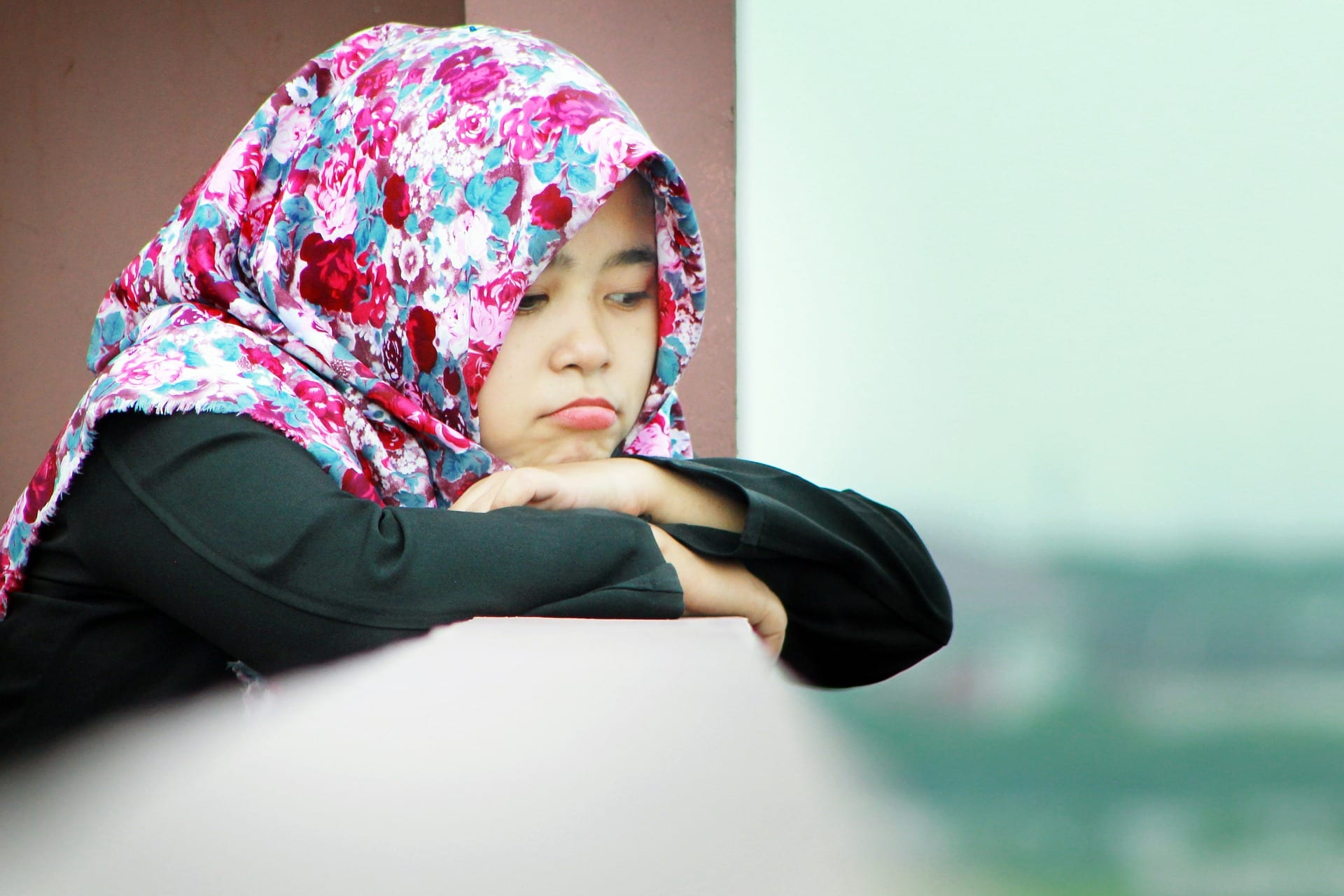 A young girl in a hijab looking forlorn.